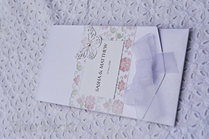 Image of Broderie Antique Rose long pocketfold invitation, decorated with flower and vine paper, organza bow , butterfly and gem.