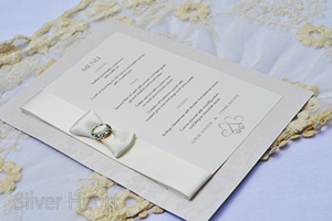 Champagne and Bows wedding menu.  Elegant broderie card with textured lace effect embellished with double faced satin ribbon dior bow, diamante buckle.