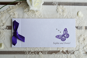Passionate Purple cheque book wedding invitation, on white borderie lace effect card, with purple butterfly, gems and satin bow.