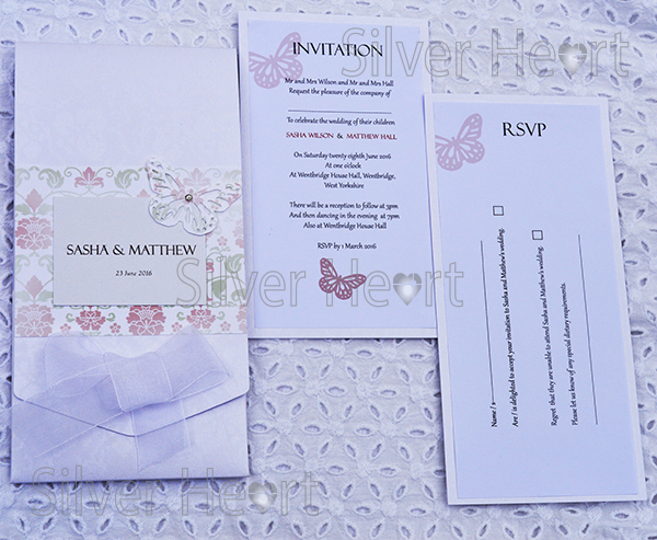 Image of Broderie Antique Rose long pocketfold invitation, decorated with flower and vine paper, organza bow , butterfly and gem. Also showing two inserts: Invitation and RSVP.