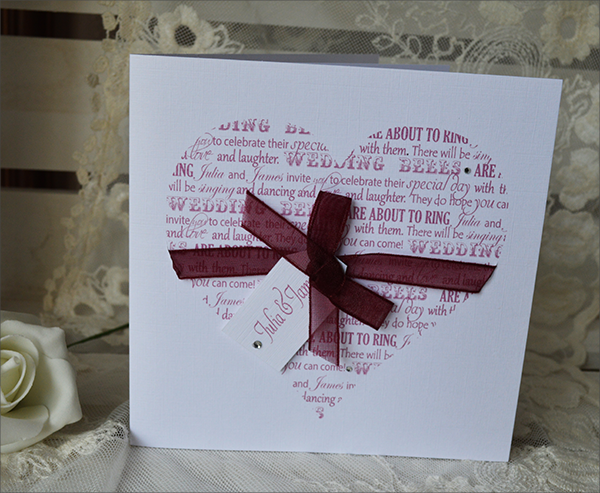 From the Heart invitation.  A linen card with a heart constructed of a variety of fonts and phrases with a wedding theme.  A gossamer bow wraps around the heart with a luggage tag attached with names of the happy couple and diamante embellishments. Colours can be adapted.