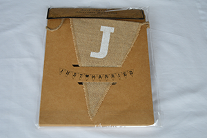 Image of hessian 'just married' bunting, with white letters on triangle shaped hessian pendants.