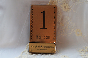 Image of a pack of kraft card table numbers with laser cut design and black art deco style numbers and writing.