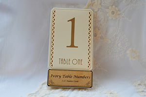 Image of a pack of ivory and gold table numbers with laser cut design and gold art deco style numbers and writing.