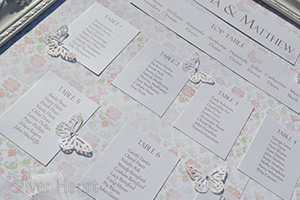 Broderie Antique Rose Table Plan with rose and vine patterned paper background , pearlescent guest lists and titles and buttefly decorations. (close up).